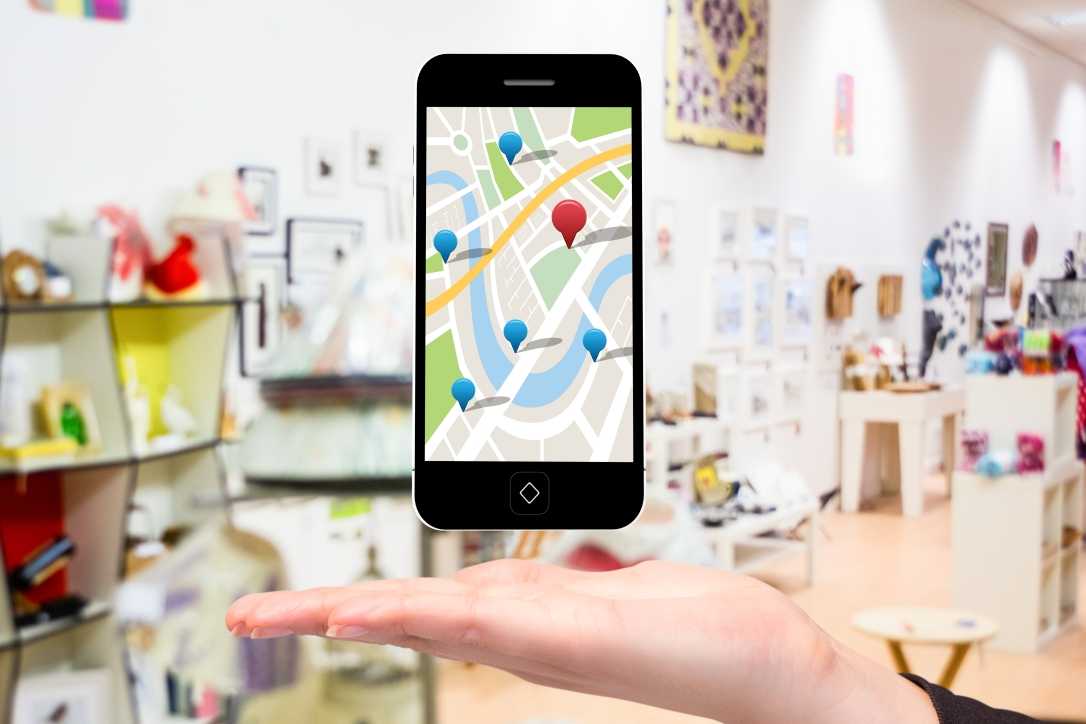 composite of hand holding smartphone with maps graphic with store background